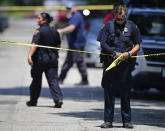 A police officer tapes off the crime scene where several bodies were found, Tuesday, July 9, 2019, in Cleveland. Police investigating the shooting death of a man in a vacant lot say they also found the bodies of a woman and two children in a nearby house. Authorities aren't saying how the three found inside the house Tuesday died, but they did say the four deaths are connected. (AP Photo/David Dermer)