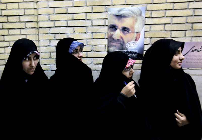 Female supporters of the Iranian presidential candidate Saeed Jalili, shown in the poster on the wall, Iran's top nuclear negotiator, waits for him, at a campaign rally attended by his female supporters, in Tehran, Iran, Wednesday, May 29, 2013. Iran will hold its 11th presidential elections after 1979 Islamic Revolution, on June 14. (AP Photo/Vahid Salemi)