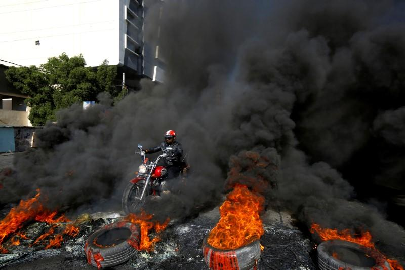 A man rides a motorcycle between burning tires during ongoing anti-government protests in Najaf