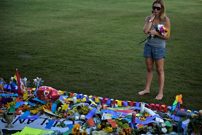 A woman stands at a memorial for the Pulse nightclub shooting victims on June 14, 2016 in Orlando, Florida (AFP Photo/Brendan Smialowski)