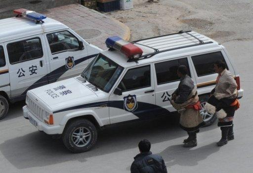Two Tibetan Buddhist pilgrims look at a police car outside the Labrang Monastery in Xiahe, Gansu Province