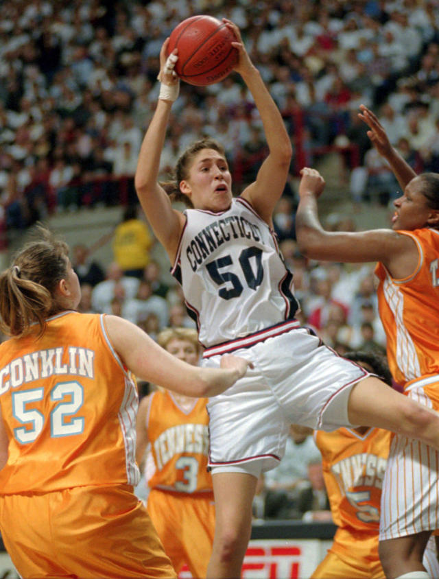 FILE - In this Jan. 16, 1995, file photo, Connecticut's Rebecca Lobo (50) pulls in a rebound as Tennessee's Abby Conklin (52) and Tiffani Johnson, right, defend during the first half of an NCAA college basketball game in Storrs, Conn. For over a decade the rivalry in women's basketball was Tennessee and UConn. After a 13-year absence the two teams will play Thursday night, Jan. 23, 2020, in Hartford, Connecticut. (AP Photo/Bob Child, File)