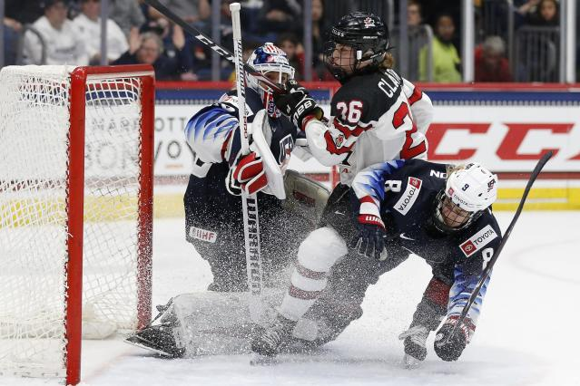 Canada's Emily Clark (26) and United States' Emily Matheson (8) collide in front of goalie Alex Cavallini during the second period of a rivalry series women's hockey game in Hartford, Conn., Saturday, Dec. 14, 2019. (AP Photo/Michael Dwyer)
