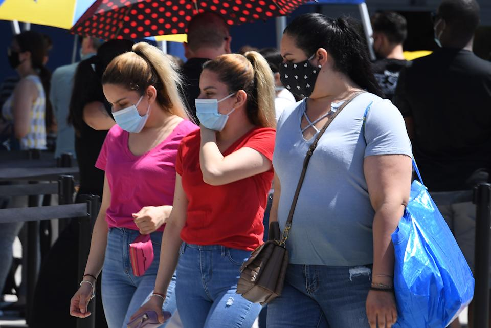 People wearing face masks wait in line to shop at Ikea in Carson, California on July 4, 2020 the US Independence Day holiday. (Photo by Robyn Beck / AFP) (Photo by ROBYN BECK/AFP via Getty Images)
