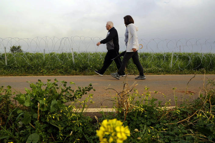 """A couple walk along a row of razor wire along the southern side of a U.N buffer zone that cuts across the ethnically divided Cyprus, during sunset near village of Astromeritis, Tuesday, March 9, 2021. The government of ethnically split Cyprus has come under fire over a decision to lay razor wire along a section of a U.N. controlled buffer zone it said is needed to stem migrant inflows from the island's breakaway north, with critics charging that the """"ineffective"""" scheme only feeds partitionist perceptions amid a renewed push resume dormant peace talks. (AP Photo/Petros Karadjias)"""