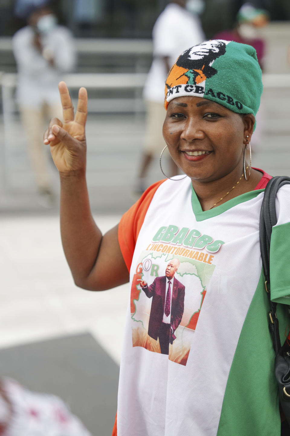A supporter of former Ivory Coast President Laurent Gbagbo gestures as she gathers with others at the Brussels international airport in Brussels, Thursday, June 17, 2021. The former Ivory Coast president Laurent Gbagbo is returning home to Ivory Coast for the first time in nearly a decade, after his acquittal on war crimes charges was upheld at the International Criminal Court earlier this year. (AP Photo/Olivier Matthys)