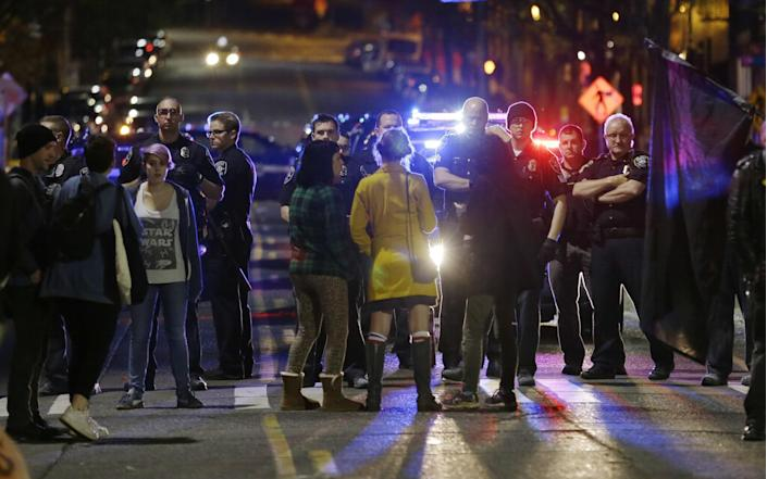 <p>Police confront protesters during a demonstration against President-elect Donald Trump, early Wednesday, Nov. 9, 2016, in Seattle's Capitol Hill neighborhood. (Photo: Ted S. Warren/AP) </p>