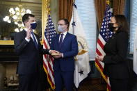 Pete Buttigieg, with his hand on the Bible held by Chasten Buttigieg, is sworn in as Transportation Secretary by Vice President Kamala Harris in the Old Executive Office Building in the White House complex in Washington, Wednesday, Feb. 3, 2021. (AP Photo/Andrew Harnik)