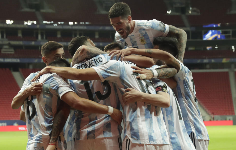 Players of Argentina celebrate their side's opening goal against Uruguay scored by teammate Guido Rodriguez during a Copa America soccer match at the National Stadium in Brasilia Brazil, Friday, June 18, 2021. (AP Photo/Eraldo Peres)