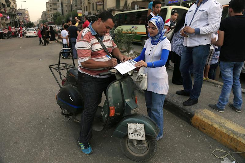 "In this Sunday, June 2, 2013 photo, an Egyptian on his motorbike signs a petition for Tamarod, Arabic for ""rebel"", a campaign calling for the ouster of Egyptian President Mohammed Morsi and for early presidential elections in the Shubra neighborhood in Cairo, Egypt. Young activists are trying to rally public discontent with Egypt's Islamist President Mohammed Morsi by fanning out in the streets and collecting millions of signatures on a petition calling for his removal. Morsi's Muslim Brotherhood has dismissed the campaign as irrelevant, even illegal, but the signature drive has stirred up Egypt's politics as the president nears the end of his tumultuous first year in office. (AP Photo/Hassan Ammar)"