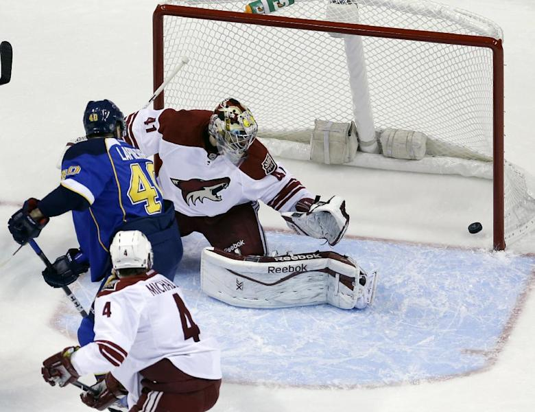 St. Louis Blues' Maxim Lapierre, center, scores on a deflection past Phoenix Coyotes goalie Mike Smith (41) as Coyotes' Zbynek Michalek (4), of Czech Republic, stands by during the first period of an NHL hockey game Tuesday, Nov. 12, 2013, in St. Louis. (AP Photo/Jeff Roberson)
