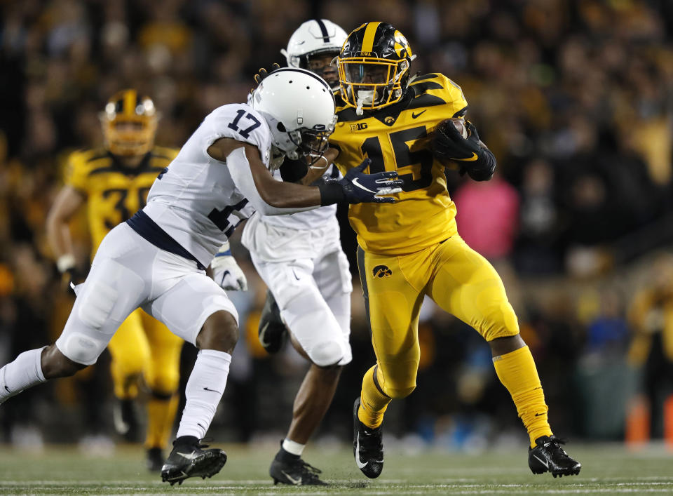 Iowa running back Tyler Goodson, right, runs the ball as he tries to fend off Penn State safety Garrett Taylor, left, during the first half of an NCAA college football game Saturday, Oct. 12, 2019, in Iowa City, Iowa. (AP Photo/Matthew Putney)