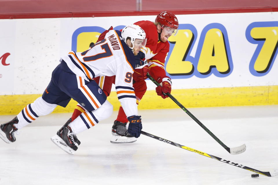 Edmonton Oilers' Connor McDavid, left, and Calgary Flames' Joakim Nordstrom reach for the puck during the first period of an NHL hockey game Saturday, April 10, 2021, in Calgary, Alberta. (Larry MacDougal/The Canadian Press via AP)