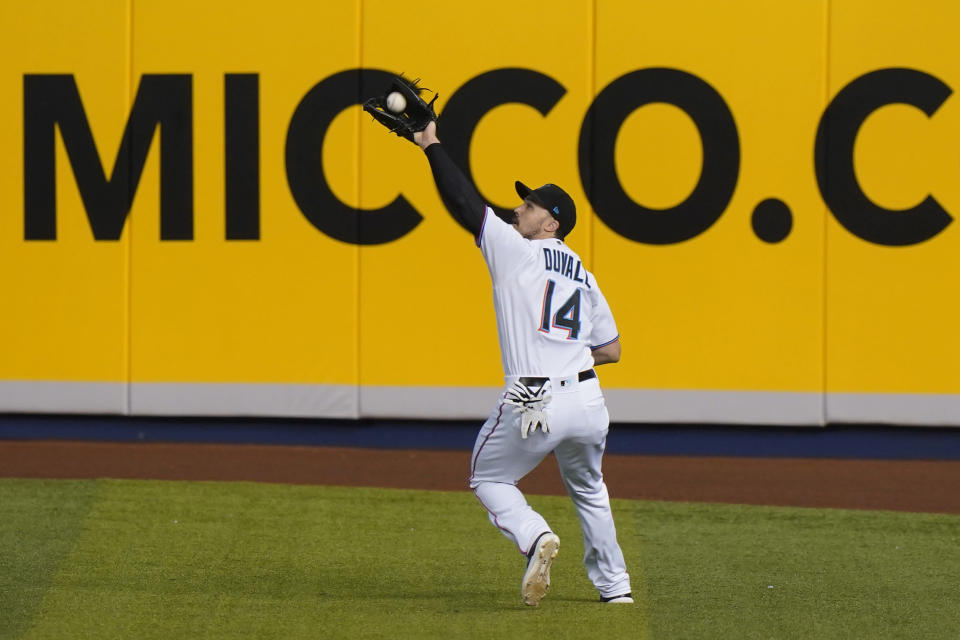 Miami Marlins right fielder Adam Duvall (14) catches a ball hit by Philadelphia Phillies' Jean Segura during the first inning of a baseball game, Monday, May 24, 2021, in Miami. (AP Photo/Wilfredo Lee)