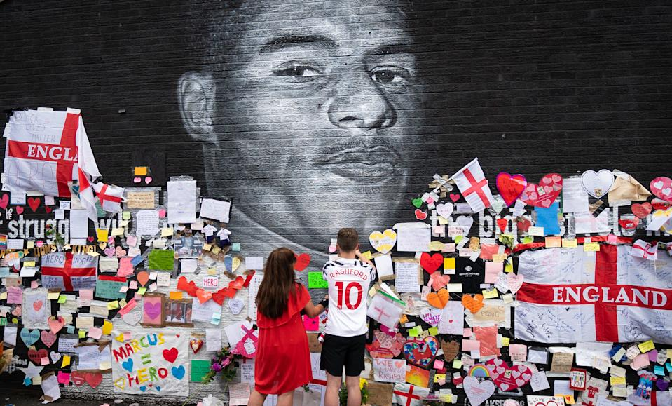 Mackenzie Robertson and his mother Sally Coles-Robertson put up a message on the mural of Manchester United striker and England player Marcus Rashford on the wall of the Coffee House Cafe on Copson Street, Withington. The mural appeared vandalised on Monday after the England football team lost the UEFA Euro 2021 final. Picture date: Tuesday July 13, 2021. Photo credit should read: Danny Lawson/PA Wire