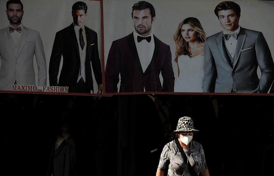 A masked woman walks along Maple Avenue in Los Angeles and an advertisement of people in formal wear is behind her.