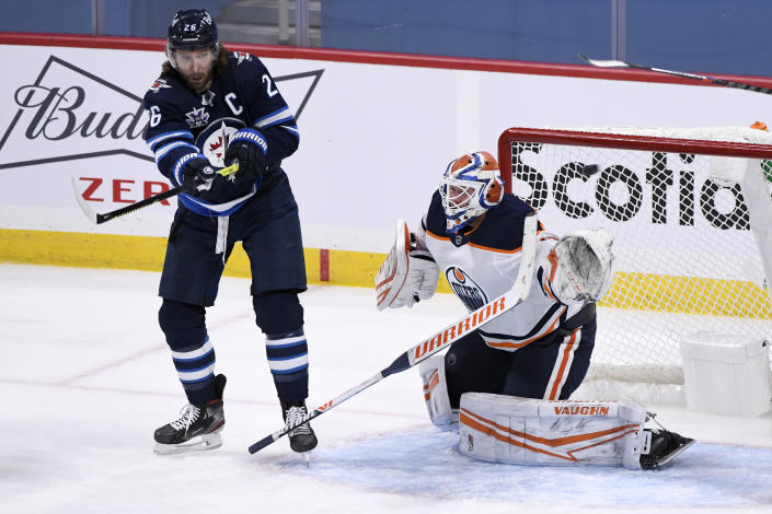Edmonton Oilers' goaltender Mikko Koskinen (19) loses his stick as the shot is deflected by Winnipeg Jets' Blake Wheeler (26) during the second period of an NHL hockey game Tuesday, Jan. 26, 2021, in Winnipeg, Manitoba. (Fred Greenslade/The Canadian Press via AP)