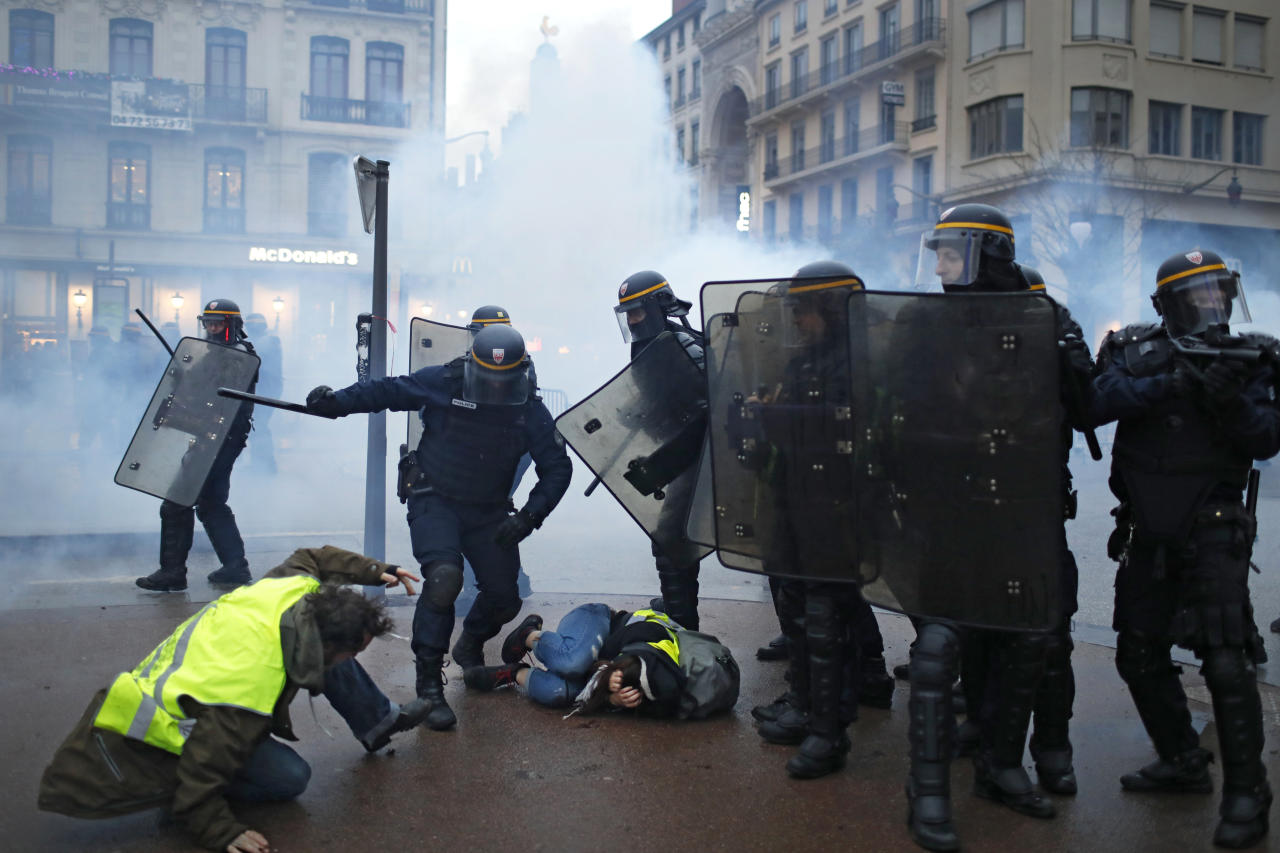 Police officers clash with demonstrators in Lyon, central France, Saturday, Dec. 8, 2018. The grassroots movement began as resistance against a rise in taxes for diesel and gasoline, but quickly expanded to encompass frustration at stagnant incomes and the growing cost of living. (AP Photo/Laurent Cipriani)