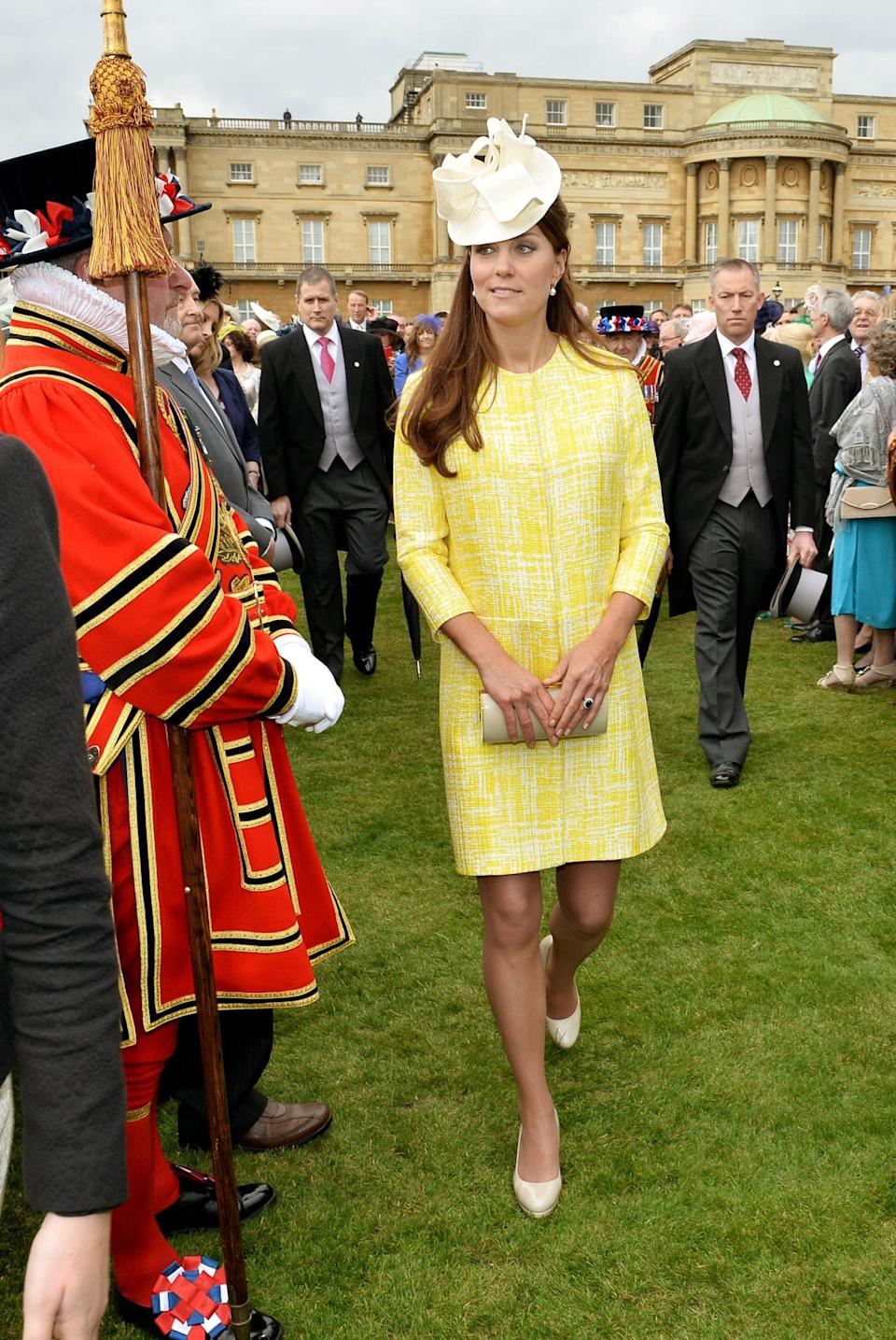 <p>Kate attended the Queen's Garden Party in a sunny yellow dress from Emilia Wickstead. She carried a beige leather Russell & Bromley clutch and finished with a white hat from Jane Corbett. </p><p><i>[Photo: PA]</i></p>
