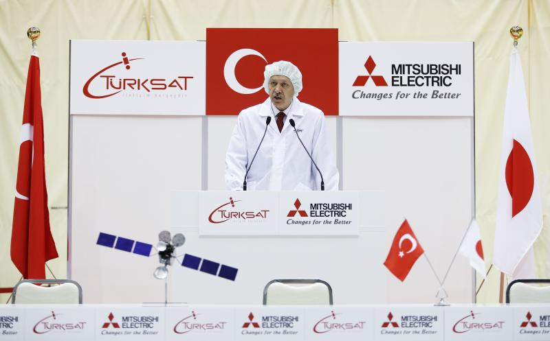 Turkey's Prime Minister Tayyip Erdogan, wearing a dust-free garment, delivers a speech during a ceremony to mark the shipment of the Turksat-4A satellite at Mitsubishi Electric Corp's Kamakura Works, the satellite production facility, in Kamakura, south of Tokyo January 8, 2014. Mitsubishi Electric Corp. made the Turksat-4A and Turksat-4B communications satellite for the operator Turksat Satellite Communication and Cable TV Operation AS (Turksat AS) and get prepared one of those for shipping on Wednesday. The Turksat-4A satellite, which is scheduled to launch in mid-February 2014 from Baikonur Space Center, will enable Turksat AS to offer telecommunication and TV broadcasting services throughout Turkey, as well as in Europe, Central Asia, the Middle East and Africa, the company official said. REUTERS/Issei Kato (JAPAN)