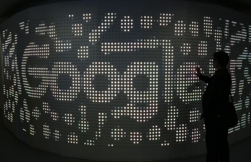 An attendee interacts with an illuminated panel at Google stand during the Mobile World Congress in Barcelona
