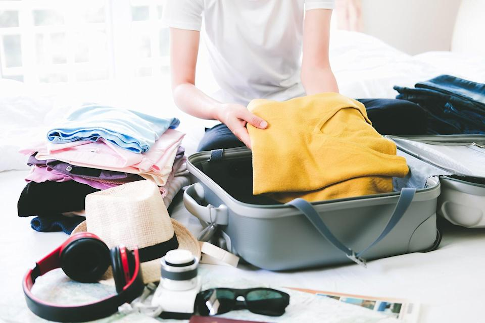 Midsection Of Woman Packing Suitcase On Bed At Home