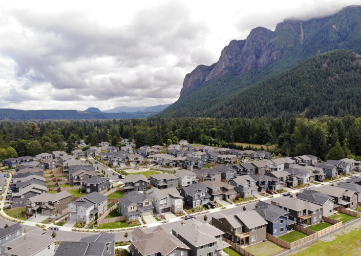 In this photo taken July 24, 2019, a development of houses stand next to a forest and in view of Mt. Si in the Cascade foothills of North Bend, Wash. The region, famous for its rainfall, has long escaped major burns even as global warming has driven an increase in both the size and number of wildfires elsewhere in the American West. But according to experts, previously too-wet-to-burn parts of the Pacific Northwest now face an increasing risk of significant wildfires because of climate change. (AP Photo/Elaine Thompson)