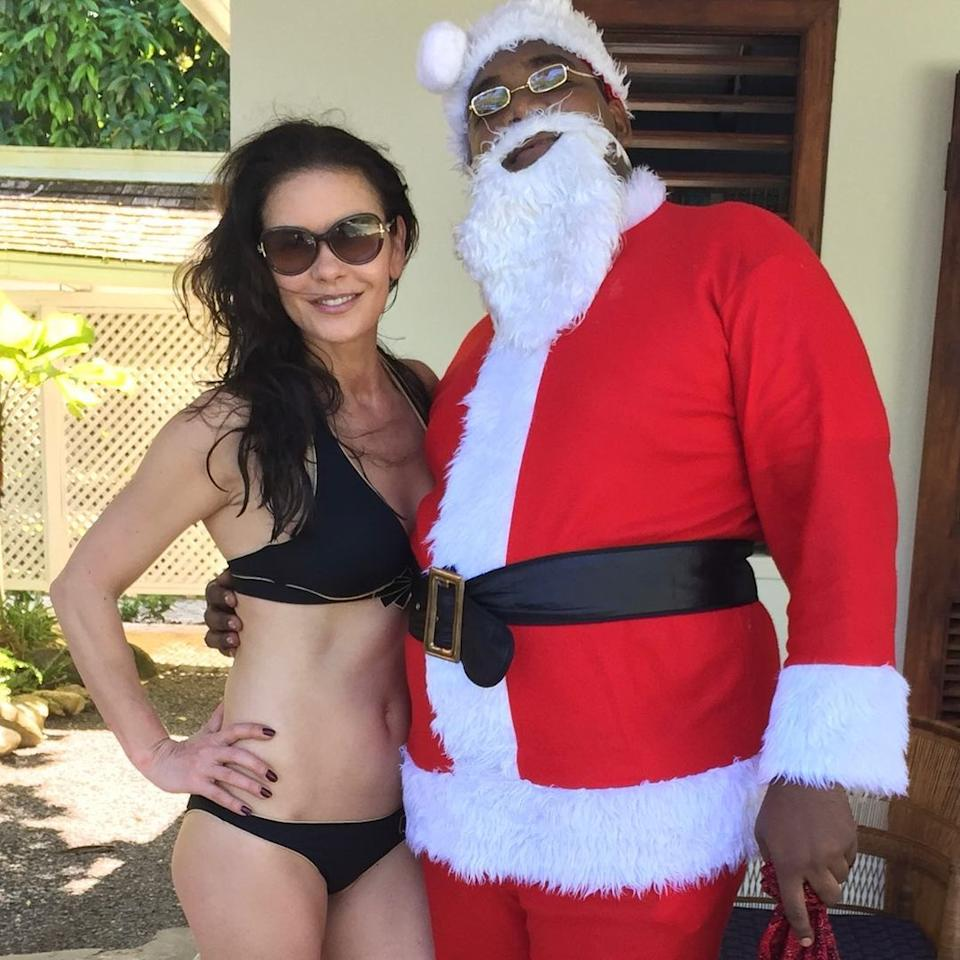 Catherine Zeta-Jones wearing a black bikini while posing with a man dressed as Santa Claus