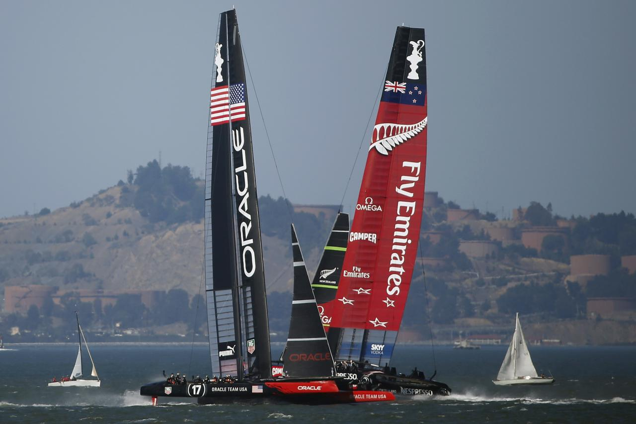 Oracle Team USA (L) follows Emirates Team New Zealand (R) during Race 18 of the 34th America's Cup yacht sailing race in San Francisco, California September 24, 2013. REUTERS/Stephen Lam (UNITED STATES - Tags: SPORT YACHTING)