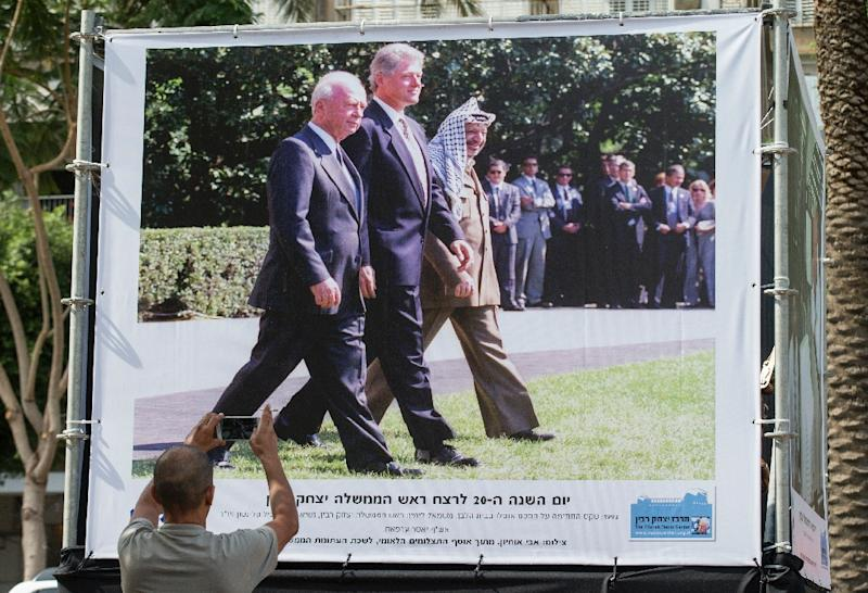 Israeli Government Press Office images of late Israeli prime minister Yitzhak Rabin (L) walking alongside former US president Bill Clinton and late Palestinian leader Yasser Arafat, are displayed at an exhibition in Tel Aviv (AFP Photo/Jack Guez)