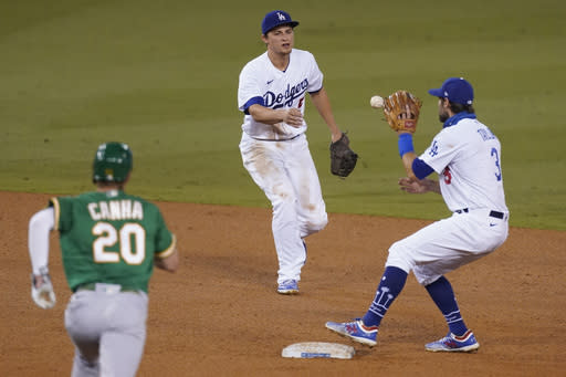 Los Angeles Dodgers shortstop Corey Seager, center, tosses the ball to second baseman Chris Taylor to put out Oakland Athletics' Mark Canha on a grounder by Jake Lamb, who was safe at first during the sixth inning of a baseball game Tuesday, Sept. 22, 2020, in Los Angeles. Lamb was safe at first. (AP Photo/Ashley Landis)