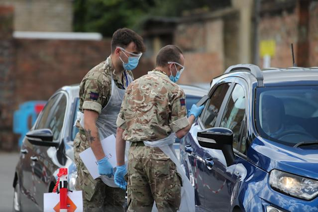 Soldiers help to conduct tests at a pop-up coronavirus drive-through testing centre in Dalston, east London. (PA)