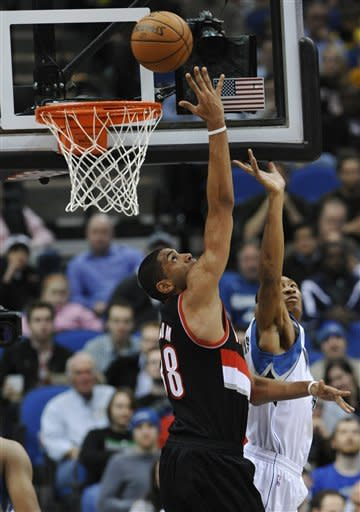 Minnesota Timberwolves' Wesley Johnson, right, defends as Portland Trail Blazers' Nicolas Batum ,of France, makes a successful reverse shot for a basket in the first half of an NBA basketball game Wednesday, March 7, 2012 in Minneapolis. (AP Photo/Jim Mone)