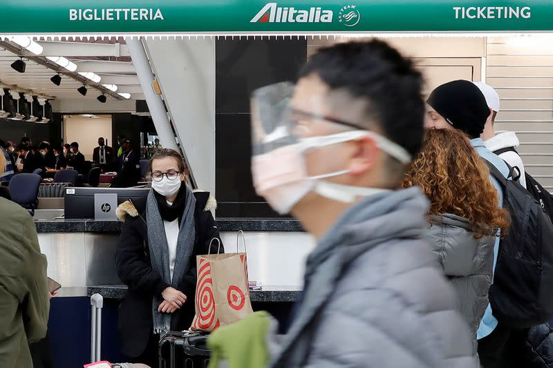 FILE PHOTO: A woman wearing a face mask waits with other passengers at the check-in area for an Alitalia, after further cases of coronavirus were confirmed in New York, at JFK International Airport in New York
