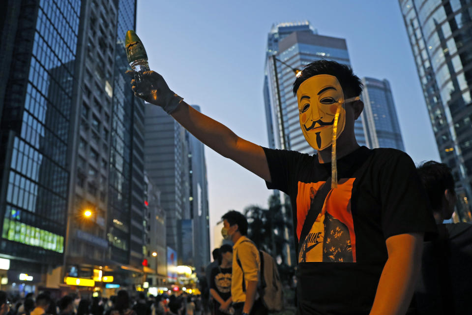 A protester wears a mask and holds up his hand as he occupied a road in Hong Kong Friday, Oct. 4, 2019. Hong Kong pro-democracy protesters marched in the city center ahead of reported plans by the city's embattled leader to deploy emergency powers to ban people from wearing masks in a bid to quash four months of anti-government demonstrations. (AP Photo/Kin Cheung)