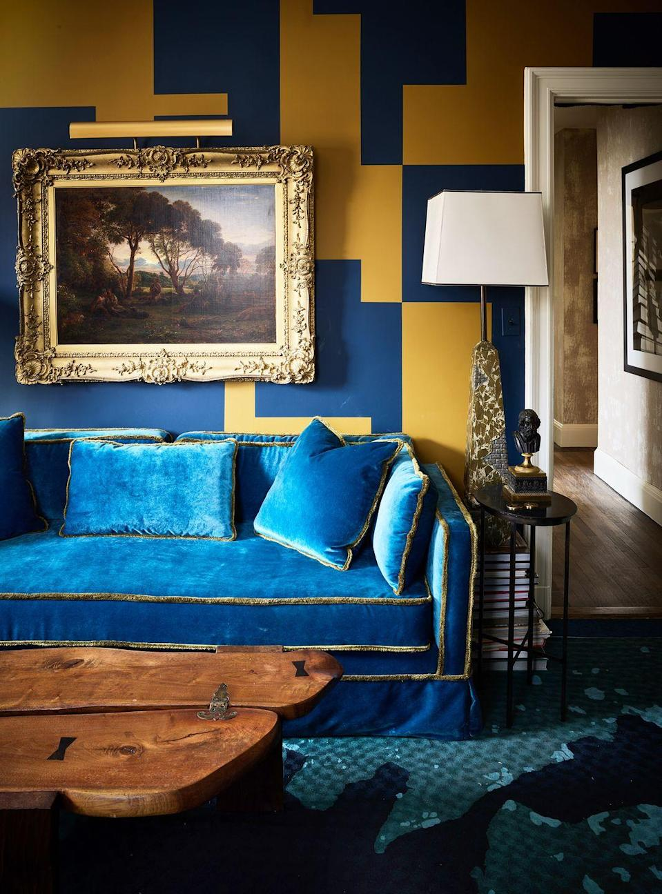 """<p><a href=""""https://www.housebeautiful.com/design-inspiration/house-tours/a33538067/ann-pyne-mcmillen-apartment/"""" rel=""""nofollow noopener"""" target=""""_blank"""" data-ylk=""""slk:Ann Pyne"""" class=""""link rapid-noclick-resp"""">Ann Pyne</a> worked with decorative painter Arthur Fowler to create a contrasting geometric pattern on the walls. """"I think of the puzzle-like shapes as a metaphor—it's a game of fitting all these disparate 'treasures' into a graphically coherent whole,"""" she says. Matte navy blue and a gritty mustard-tone work together to set a pensive and seductive backdrop—perfect for a smaller living room. </p>"""