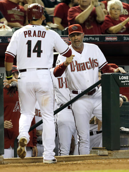 Arizona Diamondbacks' Martin Prado (14) is greeted by manager Kirk Gibson after scoring on a two-RBI single by Miguel Montero against the Los Angeles Dodgers during the third inning of a baseball game on Thursday, Sept. 19, 2013, in Phoenix. (AP Photo/Matt York)