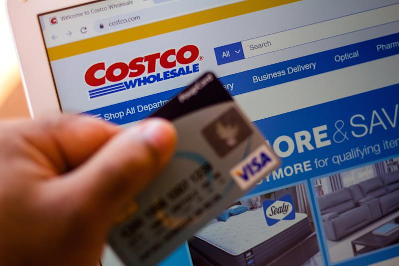 BRAZIL - 2020/07/05: The Costco Wholesale Corporation website is displayed on a laptop in the background with a hand holding a bank card. (Photo Illustration by Rafael Henrique/SOPA Images/LightRocket via Getty Images)