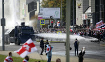 FILE In this file photo taken on Sunday, Oct. 4, 2020, Police use a water cannon agains demonstrators during a rally in Minsk, Belarus. Protests broke out Aug. 9 after an election that official results said gave Lukashenko a sixth term in office, but that opposition figures and some poll workers said were manipulated. Overall, human rights activists say more than 30,000 people have been arrested in the monthslong wave of protests and many of them were beaten. (AP Photo, File)