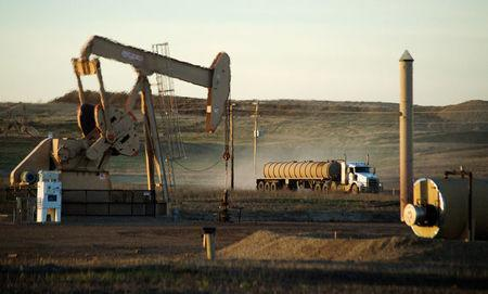 File Photo: A service truck drives past an oil well on the Fort Berthold Indian Reservation in North Dakota, November 1, 2014. REUTERS/Andrew Cullen/File Photo