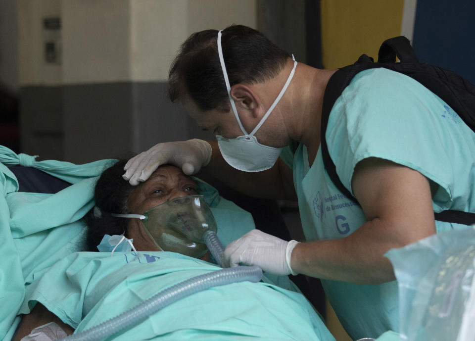 A patient is successfully evacuated from the Bonsucesso Federal Hospital while firefighters douse a blaze in Rio de Janeiro, Brazil, Tuesday, Oct. 27, 2020. According to the hospital, a 42-year-old female COVID-19 patient, who was in critical condition, died while she was being evacuated. (AP Photo/Silvia Izquierdo)
