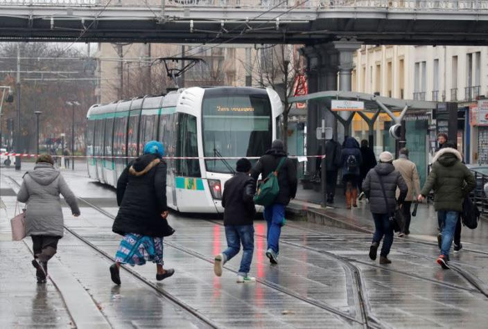 Passengers wait for a tramway during a nationwide strike by French SNCF railway workers in Paris