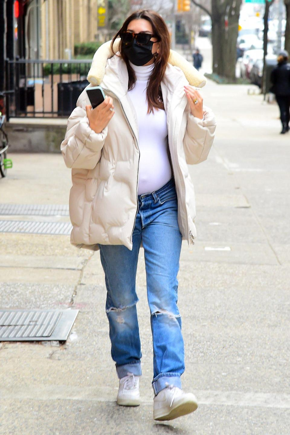 <p>Emily Ratajkowski shows off her growing baby bump in a white turtleneck and jeans on Wednesday in N.Y.C.</p>