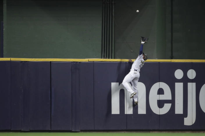 Milwaukee Brewers' Jackie Bradley Jr. makes a leaping catch at the wall on a ball hit by Atlanta Braves' Ozzie Albies during the seventh inning of a baseball game Saturday, May 15, 2021, in Milwaukee. (AP Photo/Aaron Gash)