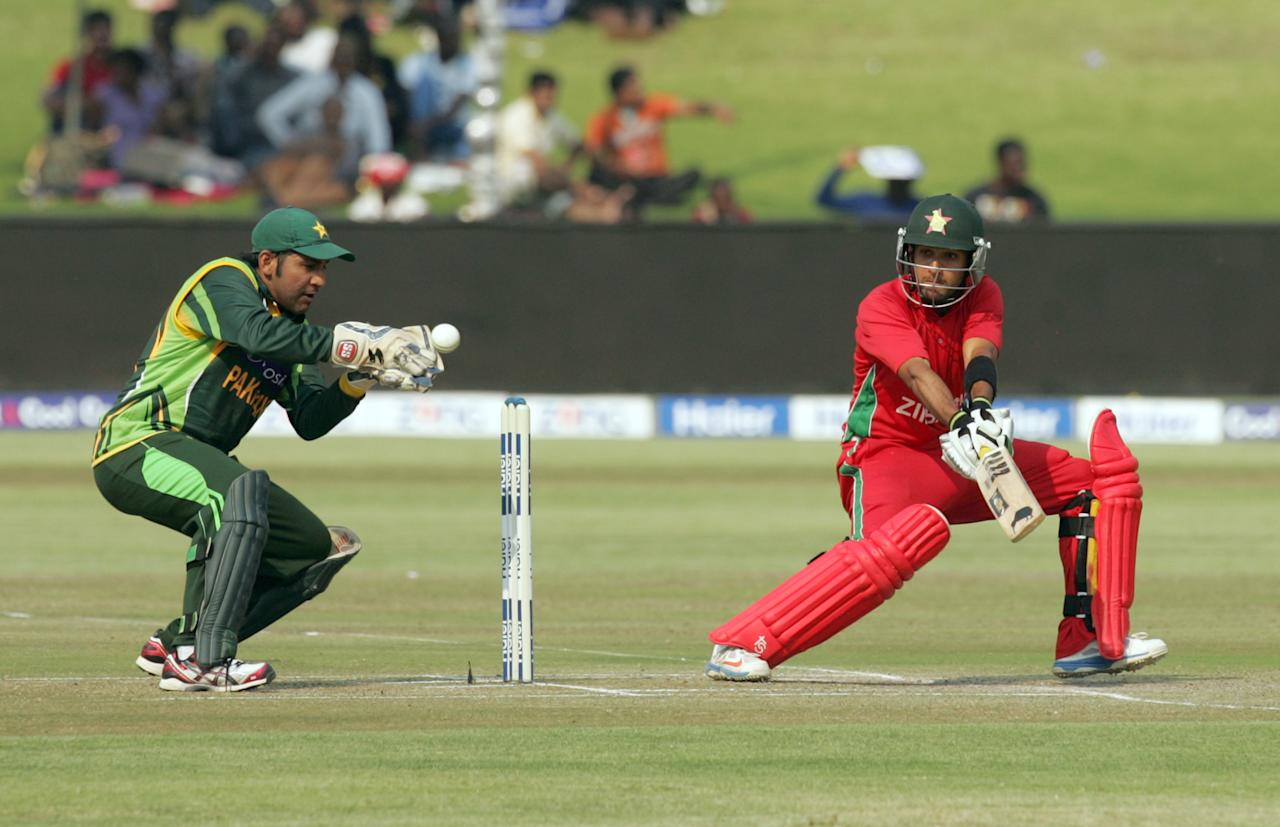 Zimbabwe batsman Sikanda Raza Butt (R) plays as Pakistan wicketkeeper Sarfraz Ahmed fields behind the stumps on August 31, 2013 during the third and final one-day international at the Harare Sports Club. AFP PHOTO / JEKESAI NJIKIZANA        (Photo credit should read JEKESAI NJIKIZANA/AFP/Getty Images)