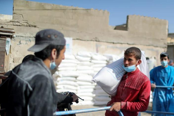 Palestinians receive food supplies at UNRWA distribution center in Gaza