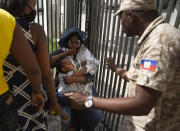 A Haitian police asks a woman to move away from a gate at the U.S. Embassy in Port-au-Prince, Haiti, Friday, July 9, 2021. A large crowd gathered outside the embassy amid rumors on radio and social media that the U.S. will be handing out exile and humanitarian visas, two days after Haitian President Jovenel Moise was assassinated in his home. (AP Photo/Joseph Odelyn)