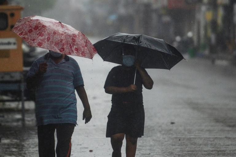 Residents walk along a road as Cyclone Nivar approached the southeastern Indian coast in Puducherry on November 25, 2020