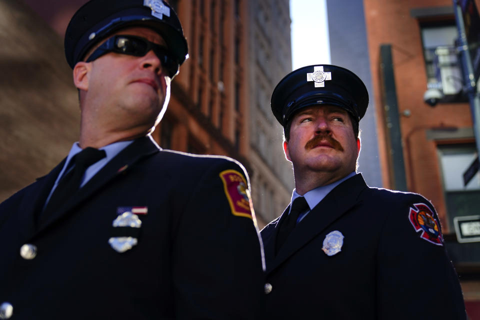Firefighters from Massachusetts gather with others outside the National September 11 Memorial and Museum during a ceremony marking the 20th anniversary of the 9/11 terrorist attacks, Saturday, Sept. 11, 2021, in New York. (AP Photo/Matt Rourke)