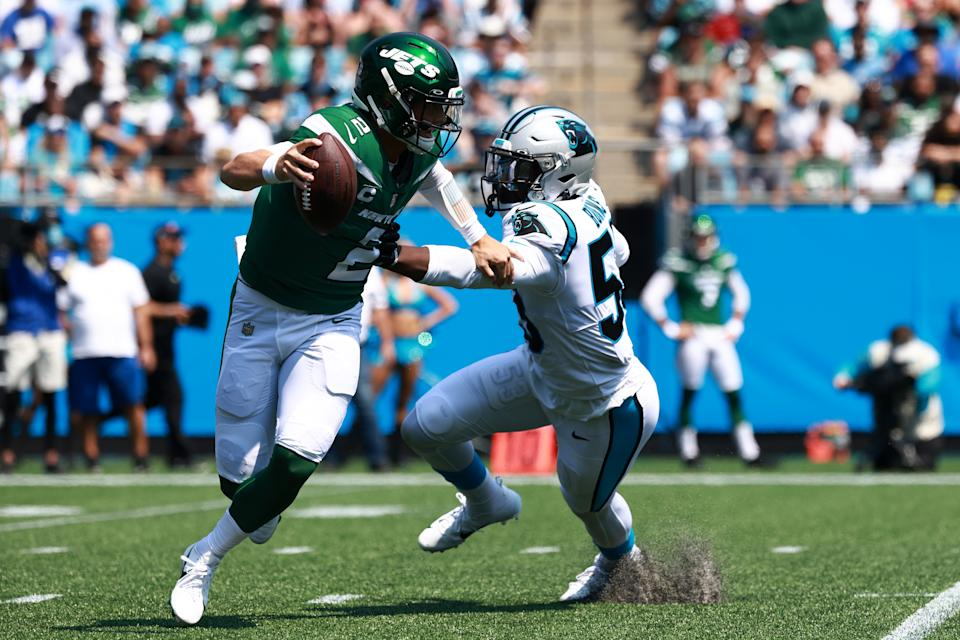 CHARLOTTE, NORTH CAROLINA - SEPTEMBER 12: Zach Wilson #2 of the New York Jets stiff arms Brian Burns #53 of the Carolina Panthers during the first quarter at Bank of America Stadium on September 12, 2021 in Charlotte, North Carolina. (Photo by Grant Halverson/Getty Images)